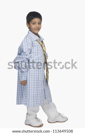 Portrait of a boy wearing oversized shirt and tie - stock photo
