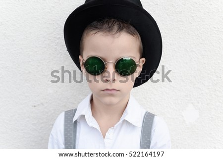 portrait of a boy with a cylinder hat and round sunglasses