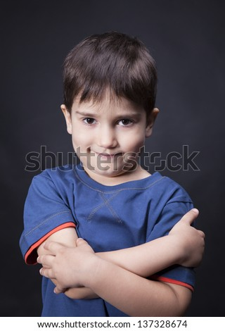 Portrait of a boy with a skeptical look on his face and crossed arms