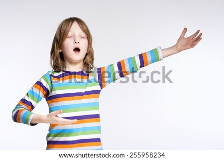 Portrait of a Boy with Blond Hair Acting as Opera Singer - stock photo