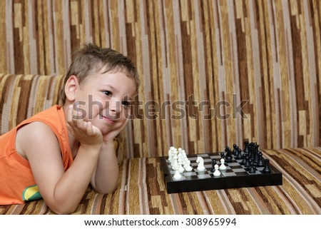 Portrait of a boy with chess on the sofa - stock photo