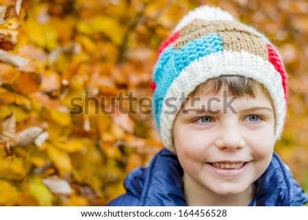 portrait of a boy with colorful autumn leaves in the background - stock photo