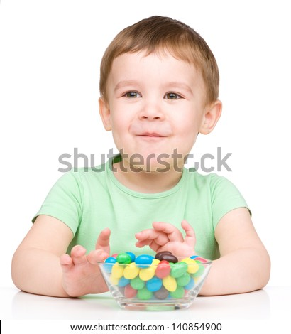 Portrait of a boy with colorful candies, isolated over white - stock photo
