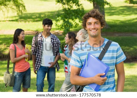 Portrait of a boy with happy college friends in background at the campus - stock photo