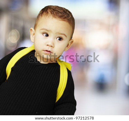 portrait of a boy with his yellow backpack against a street background - stock photo