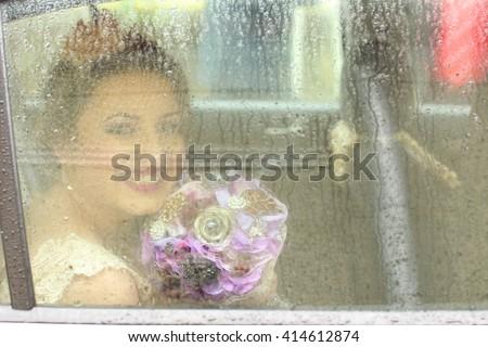 portrait  of a bride trough a wet car's window - stock photo