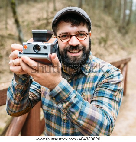 Portrait of a bright pleasant smiling male photographer with film cameras, on a wooden bridge in a picturesque forest, hipster, life style, trips