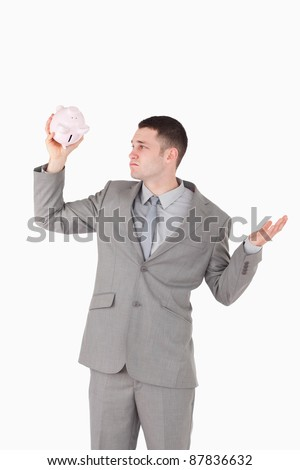 Portrait of a broke businessman looking at an empty piggy bank against a white background