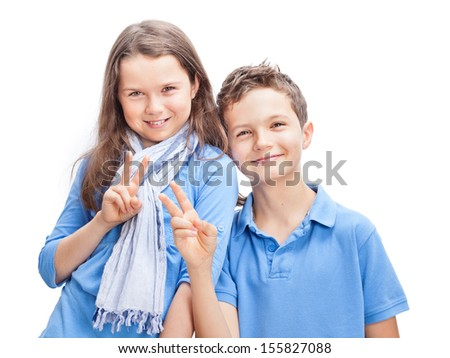 Portrait of a Brother and Sister, both wearing a blue shirt and giving the Victory sign. - stock photo