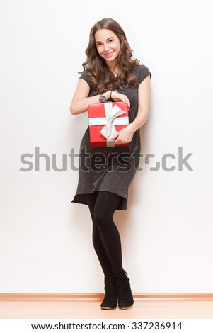Portrait of a brunette beauty holding red gift box. - stock photo