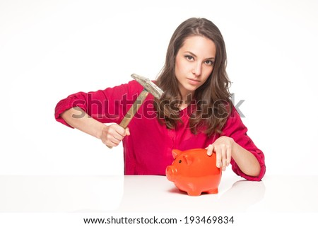Portrait of a brunette beauty posing with orange piggy bank.