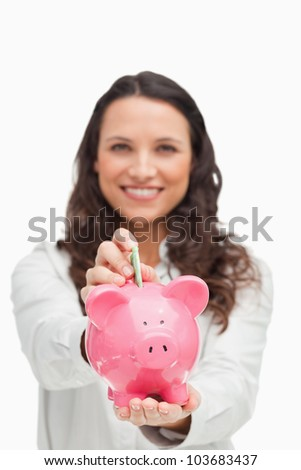 Portrait of a brunette putting money in the piggy bank against white background
