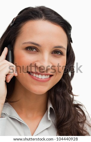 Portrait of a brunette smiling while calling against white background