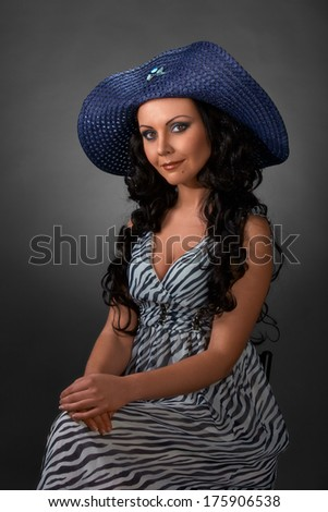 Portrait of a brunette with long curly hair in a hat, posing in studio