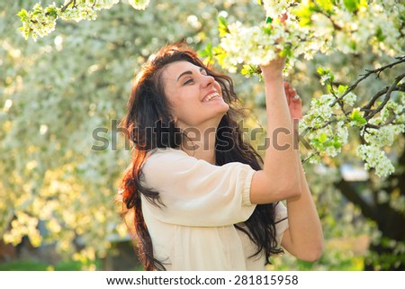 Portrait of a brunette woman inhales the scent of flowers. Happy woman enjoying the scent of blooming flowers on the tree. Young beautiful happy girl. She rests and enjoys the scent of flowers. Story. - stock photo