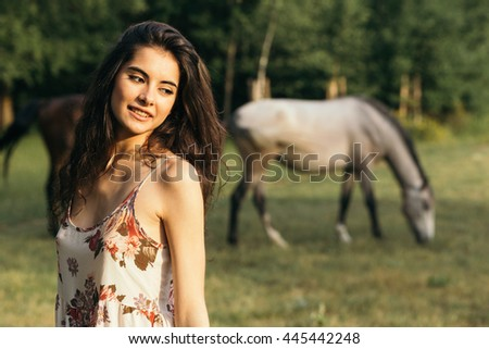 Portrait of a brunette young girl in nature wearing a dress with horses in the background - stock photo