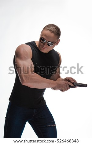 Portrait of a brutal man bodybuilder with long hair with a gun on a white background