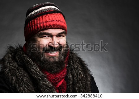 Portrait of a brutal mature man clothed in winter clothes on a dark background - stock photo