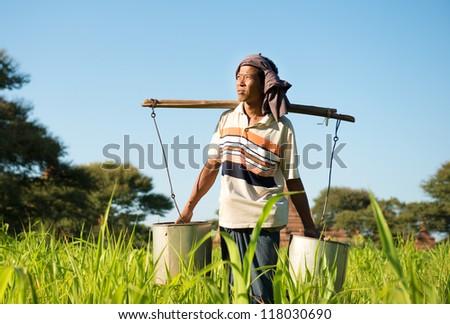 Portrait of a Burmese farmer watering plant - stock photo
