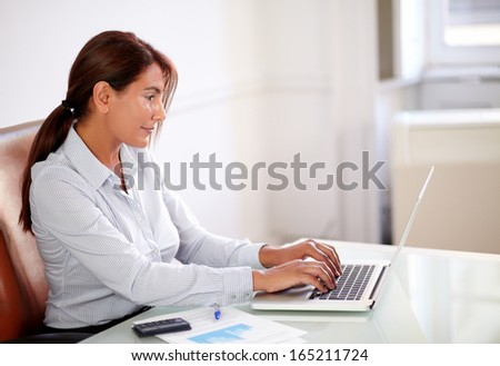 Portrait of a business lady on blue blouse working with her laptop while sitting on office desk