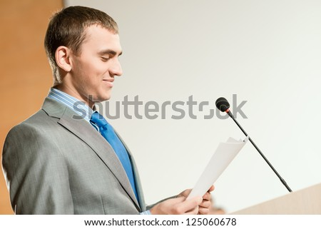 Portrait of a business man holding documents and looks at them - stock photo