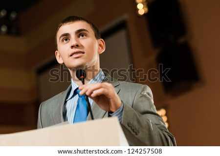 Portrait of a business man holding microphone on conference, speaks into the microphone and looks into the room - stock photo