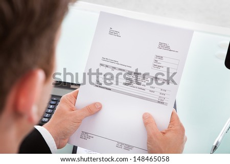 Portrait of a business man looking at invoice paper - stock photo