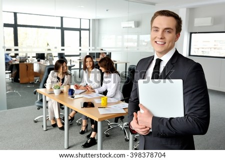 Portrait of a business man smiling at you with his colleagues in the background. - stock photo