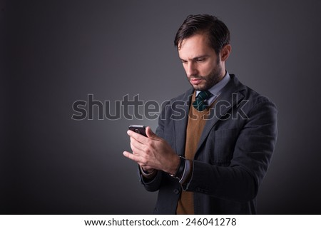 Portrait of a business man with phone on dark gray background. Studio shot.