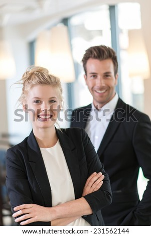portrait of a business team at office looking at camera, executive woman at foreground and man at the background - stock photo