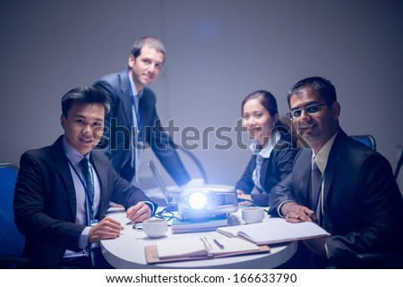 Portrait of a business team at the company'??s presentation with a projector on the foreground - stock photo