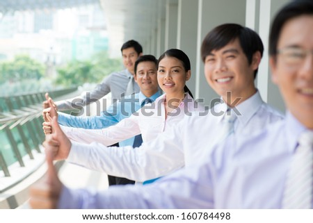 Portrait of a business team in success showing thumb-up on the foreground - stock photo