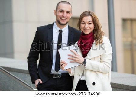 Portrait of a business woman against a blurred background with a man and office building. Business hours. Female student intern. Business people - man and woman. Successful group of business people.  - stock photo