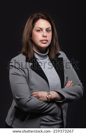 Portrait of a business woman against dark background.