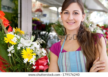 Portrait of a business woman florist working at her flower market shop and feeling proud standing with her arms crossed in front of her small business, outdoors. Business person.