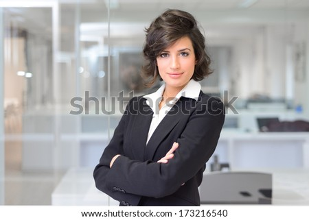 Portrait of a business woman in an office. Crossed arms - stock photo