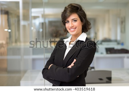 Portrait of a business woman in an office. Crossed arms