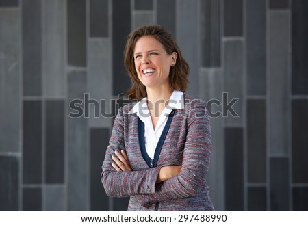 Portrait of a business woman smiling with arms crossed against gray background - stock photo