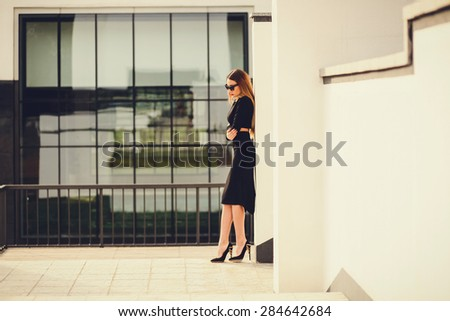 Portrait of a business woman standing near office buildings. waiting for a business meeting