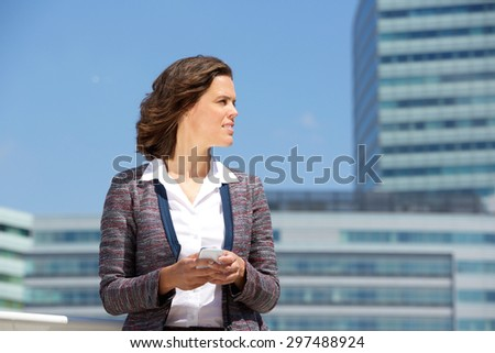 Portrait of a business woman standing outside in the city with cell phone - stock photo