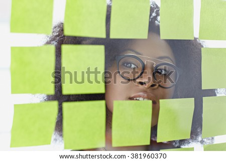 Portrait of a business woman with an afro behind sticky notes in bright glass office - stock photo