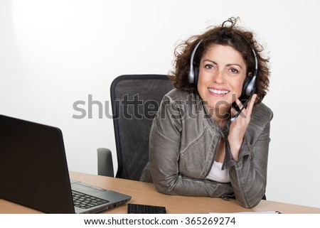 Portrait of a business woman working at her desk with a headset and laptop