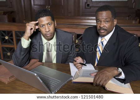 Portrait of a businessman and advocate sitting together in courtroom - stock photo
