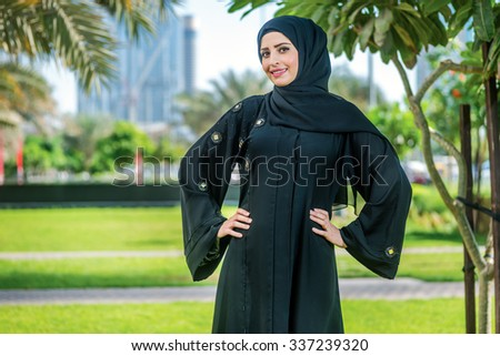Portrait of a businessman. Arab businesswoman wearing hijab poses for the camera on the background of skyscrapers of Dubai. The woman is dressed in a black abaya - stock photo