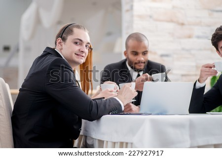 Portrait of a businessman at a meeting. Four smiling successful businessmen sitting at table in office while discussing their business doings. Young people drink coffee in the office