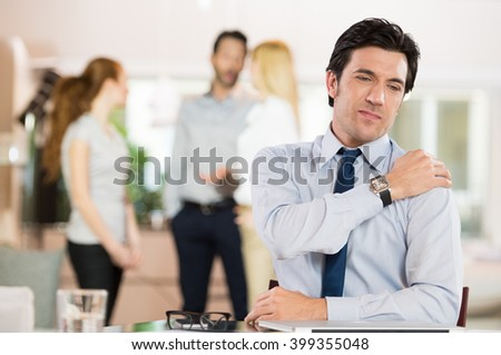 Portrait of a businessman at work suffering from shoulder pain. Portrait of stressed man holding shoulder and stretching after work. Mature business man tired and stressed after working for long.