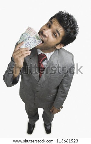 Portrait of a businessman biting Indian currency notes