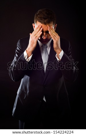 Portrait of a businessman concerned about crisis on black background