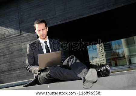 Portrait of a businessman concerned about crisis typing in a laptop computer - stock photo