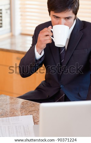 Portrait of a businessman drinking coffee while using a laptop in his kitchen - stock photo